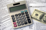calculator and American hundred dollar bill on federal 1040 income tax forms - 182633493