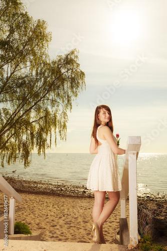 Fototapeta Woman standing on beach holding pink tulip