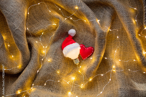 bulb in Christmas hat and heart shape toy