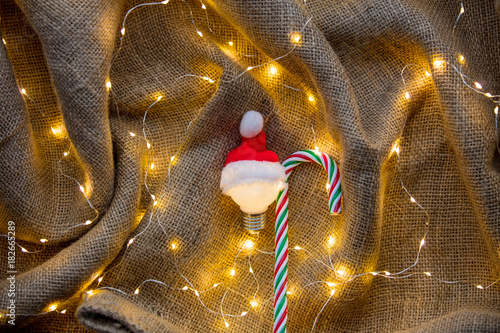 Bulb in Santa Claus hat and candy cone