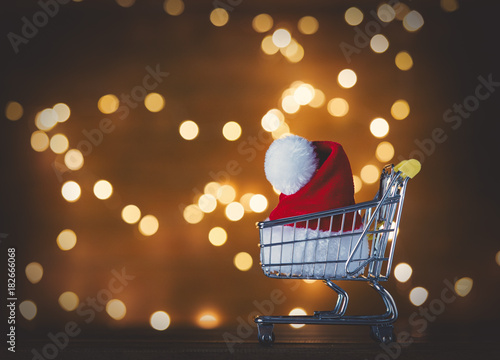 Santa Claus hat in shopping cart and Christmas Lights