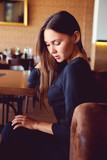 Young brunette sitting in a restaurant - 182672644