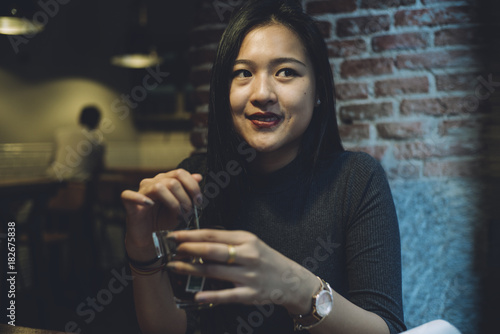 Fototapeta Asian woman drinks tea in work room.