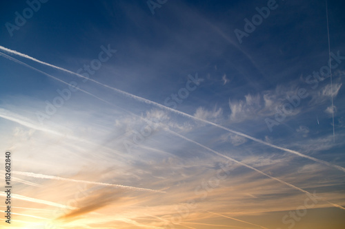 traces of an airplane at sunset as background