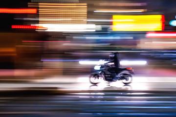 Motocicletta che sfreccia veloce di notte per le vie con luci colorate di una  grande città metropolitana