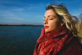 Portrait of young woman by the lake wrap around in a red blanket. - 182688892