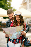 Young Tourist Couple Looking For Attractions On Map.