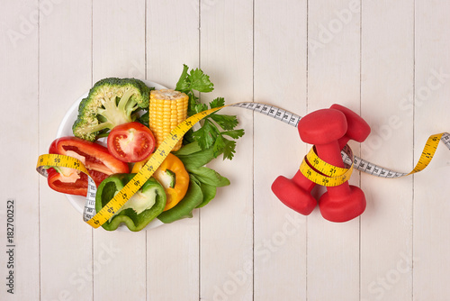 Plexiglas Fitness Bell pepper with measuring tape, dumbbells and bottle of water, isolated on white