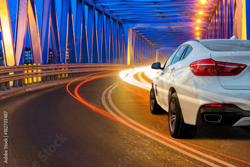 Fototapeta modern SUV driving across the bridge at night