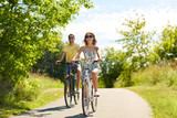 happy young couple riding bicycles in summer - 182705699