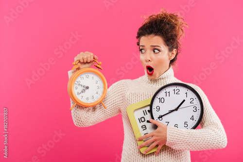 Portrait of a shocked pretty woman holding alarm clocks Poster