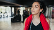 Horizontal portrait young Caucasian woman runner resting after workout session in the gym. Female jogger taking a break from running workout. People, sport and fitness concept.