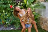 Best friends teen girls piggyback on backyard - 182718894