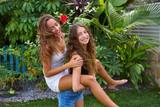 Best friends teen girls piggyback on backyard - 182719038