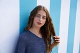 Brunette teen girl portrait in blue stripes wall - 182719439
