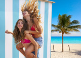 Best friends girls piggyback in summer beach - 182721014