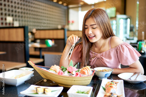 Staande foto Sushi bar Beautiful asian woman eating sashimi, Japanese food.