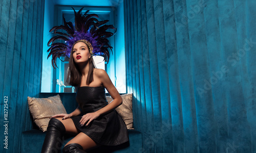 Foto op Plexiglas womenART Luxury party and celebration concept - beautiful woman in black dress and in the Brazilian accessories in club with blue background
