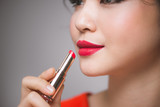 Close up portrait of attractive girl holding red lipstick over grey background - 182725834