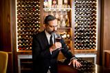 Portrait of handsome elegant businessman drinking red wine in bar - 182726631