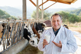 Male farmer is holding glass of cow milk at the cow farm. - 182730211
