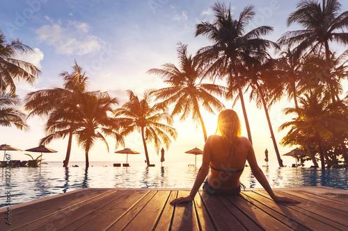 Leinwandbild Motiv Woman enjoying vacation holidays luxurious beachfront hotel resort swimming pool