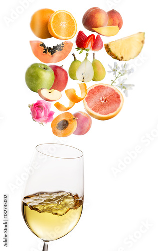 Conceptual fruit aromas floating above white wine glass.