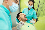 Dentists examining and working on male patient.Dentist's office. - 182738638