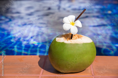 Fotobehang Plumeria Fresh coconut juice with straw and plumeria, frangipani flower on border of a swimming pool
