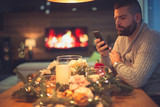 Bearded man photographing decorated christmas table - 182740267