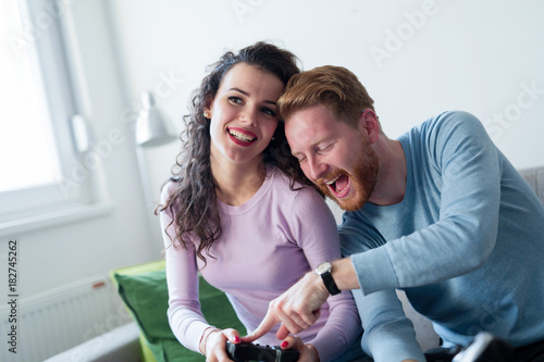 Young couple having fun playing video games Poster