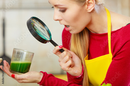 Poster Sap Woman looking at green juice through magnifer