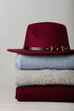 Pile of knitted clothes (sweaters, scarves, pullovers) blue, burgundy, gray colors and hat. - 182751289