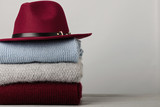 Fototapety Pile of knitted clothes (sweaters, scarves, pullovers) blue, burgundy, gray colors and hat.
