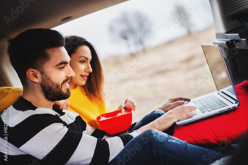 Portrait of happy young attractive love couple watching a movie on a laptop with a popcorn while having picknick in a car.