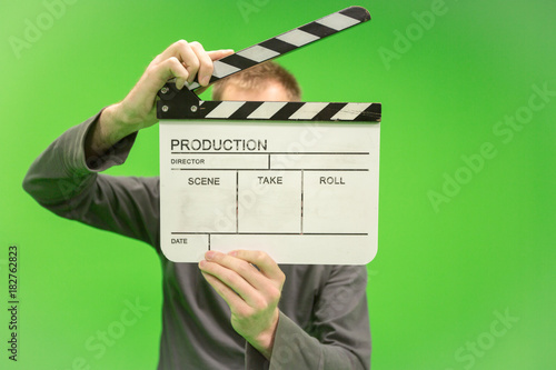 Video producer man holding movie clapper board on green background - 182762823