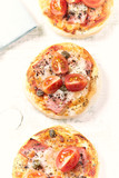Home baked mini pizza topped with ham, cherry tomatoes and capers on wooden background (from top) - 182763403