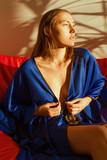 Beautiful girl in blue silk robe resting in the sunlight - 182768446