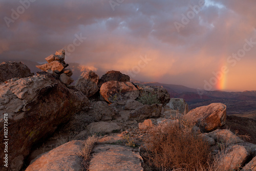 Foto op Canvas Zalm Ridge with broken boulders, some stacked into a cairn. A few desert plants grow between them at sunset with a passing storm and a rainbow in the distance.