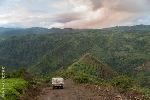 Tuinposter Cappuccino fruit truck crossing in the intricate hills with a beautiful view of the Colombian landscape