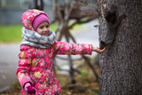 Little girl with hand feeding a squirrel in the Park. - 182776233