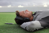 Happy man listening to phone music with headphones relaxing sleeping or meditating on green grass lying down enjoying summer day in park. Young adult using mindfulness smartphone app concept. - 182787076