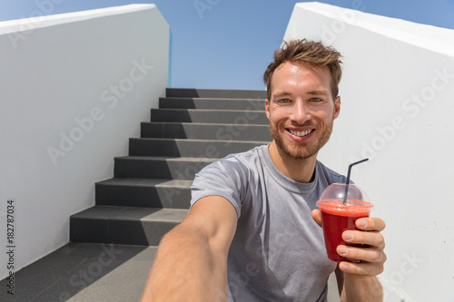 Papiers peints Jus, Sirop Healthy eating man drinking beet juice smoothie in urban city background. Active lifestyle fitness runner eating breakfast vegetable shake on stairs after run.