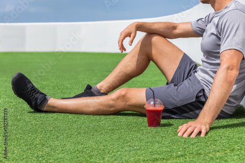 Foto op Canvas Sap Juice smoothie sport man relaxing enjoying post workout morning breakfast sitting on outdoor grass at home or fitness gym. Athlete drinking red fruit smoothie drink.
