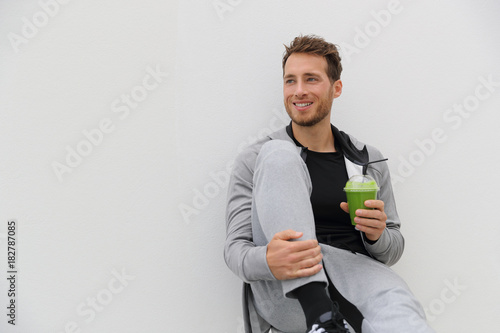 Poster Sap Healthy man drinking green smoothie post workout at gym. Sport athlete with spinach cold pressed juice plastic cup drink relaxing on white background.