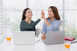 Businesspeople giving high five in the office
