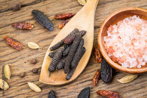 Nahaufnahme von Stangenpfeffer auf einem Kochlöffel aus Holz und rosafarbenen Kristallsalz in einer kleinen Holzschale auf rustikalem Holzhintergrund
