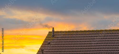 Foto op Canvas Ochtendgloren Smoking chimney on a roof at sunrise in autumn