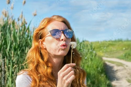 Fototapeta red-haired girl in sunglasses blows away dandelion