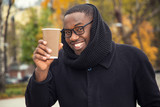Young afro american male with a paper cup of hot coffee in an autumn day. - 182818896